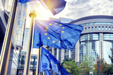 EU flags waving in front of European Parliament building in Brus