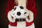 Fototapety Composite image of santa holds a classic football
