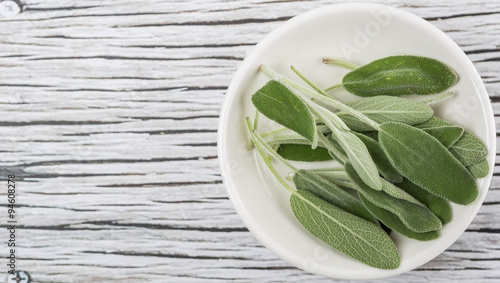 Sage leaves herb in white bowl over wooden background