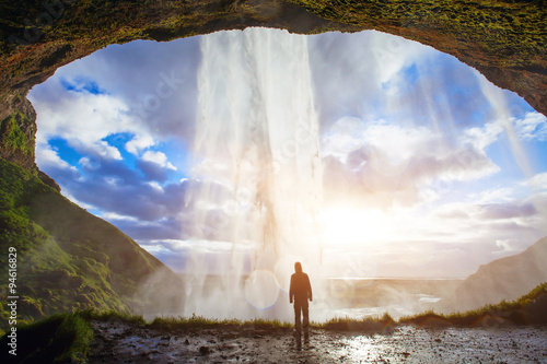 incredible waterfall in Iceland, silhouette of man enjoying amazing view of nature - 94616829