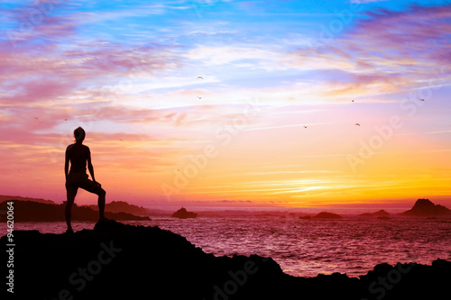 wellbeing concept, silhouette of person enjoying beautiful sunset with view of ocean