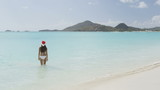 Woman in Christmas Santa hat on beach travel vacation getaway enjoying view of tropical beach turquoise paradise beach in the Caribbean. Beautiful girl in bikini under the sun. RED EPIC.