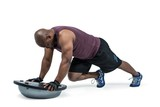 Fit man exercising with bosu ball