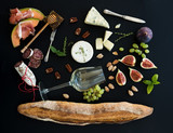 Fototapety Wine and snack set. Baguette, glass of white, figs, grapes, nuts, cheese variety, meat appetizers, herbs on black grunge background, top view