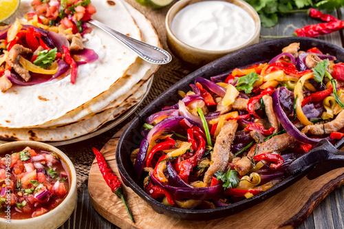 Póster Pork fajitas with onions and colored pepper, served with tortill