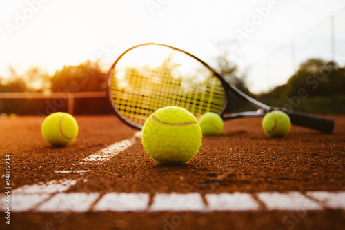 Plagát Tennis balls with racket on clay court