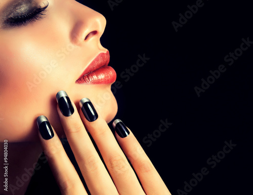 Papiers peints Manicure Beautiful model brunette shows black and silver French manicure on nails. Luxury fashion style, manicure nail , cosmetics and makeup .