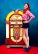 Girl in dress and hairstyle 60s-style, posing in front of a jukebox perfect reproduction of that historical period.
