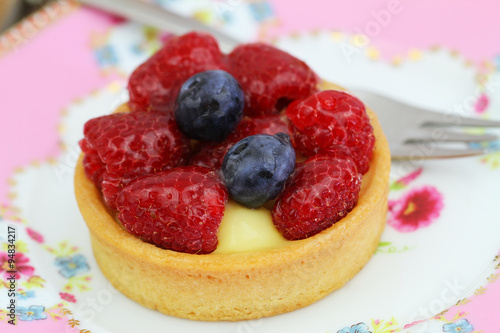 ... tartelette with custard, fresh raspberries and blueberries, closeup