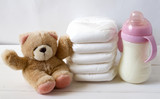 New born child stack of diapers, tebby bear toy and baby feeding bottle with milk on a white wooden background