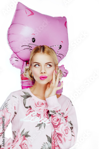 Poster Pretty cute young blond girl posing in studio, looking at camera taking in hands a balloon pink cat