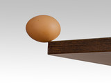 Egg teetering on the edge. Brink. Risk, danger concept or metaphor