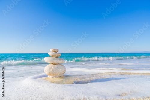Fotobehang Zen Stenen Stones pyramid on sand symbolizing zen, harmony, balance. Ocean