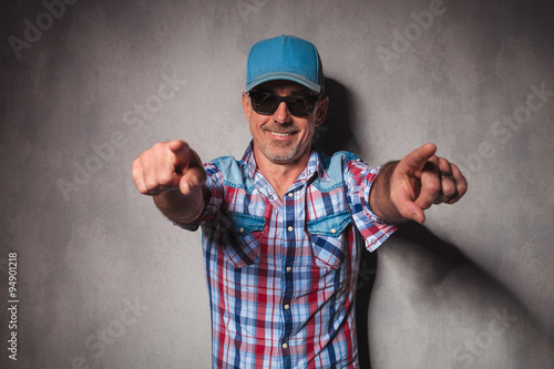 Poster cool mature casual man with trucker hat  pointing his fingers