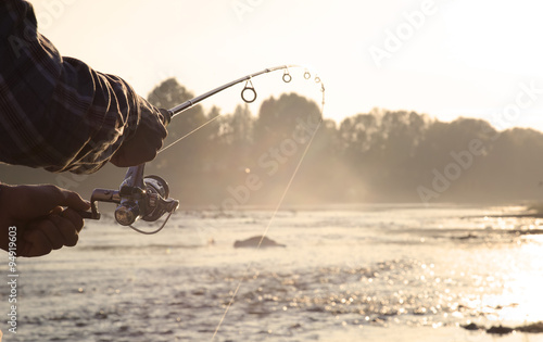 the fisherman is fishing on a river in the early morning.