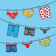 A set of a variety of colorful, cartoon underwear hang to dry on an outdoor clothesline.