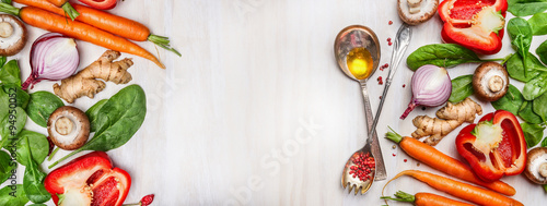Organic vegetables assorted with cooking spoons and oil on white wooden background