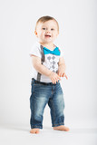 a cute 1 year old stands in a white studio setting. The boy has a happy expression. He is dressed in Tshirt, jeans, suspenders and blue bow tie