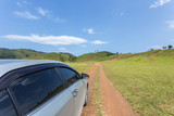 Silver car parking at the grass hill in Ranong province