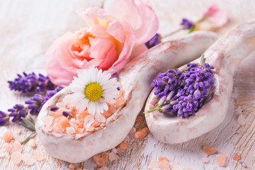 Beautiful spa still life with bathing salt, lavender, rose and daisy flower on wood