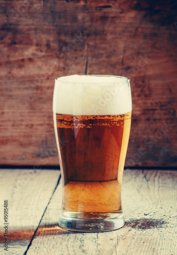 Poster large glass of light beer with foam on the old wooden background
