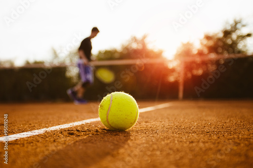 Poster Tennis ball and silhouette of player on a clay court
