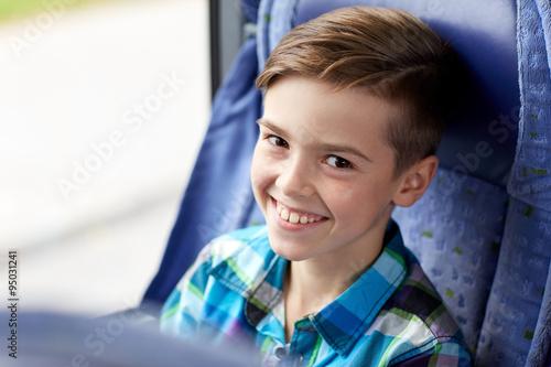 happy boy sitting in travel bus or train