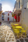 Mykonos streetview at sunrise with chapel and yellow chairs and tables, Greece