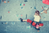 little girl climbing a rock wall