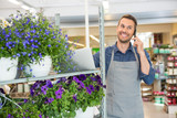 Florist Taking Order On Mobile Phone In Flower Shop
