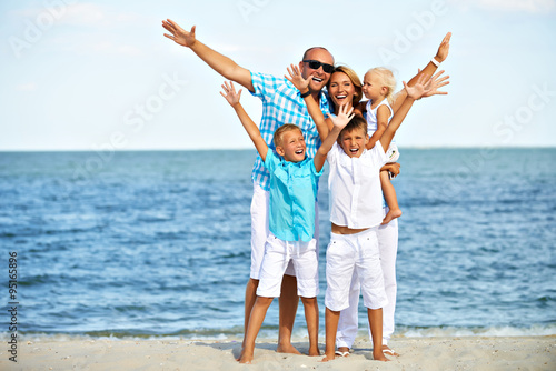 Smiling family with children having fun on the beach.