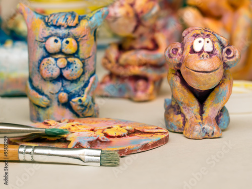 Paintbrush, clay panel and clay figurines of cat and monkey Poster