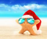 Fototapety Starfish in sunglasses on summer beach and santa hat. Merry Christmas.