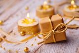 Fototapety Christmas gift box and burning candles on wood