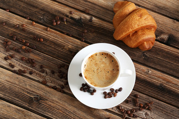 Delicious croissant with cup of coffee on brown wooden backgroun © 5second