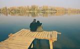 Love Couple on Wooden Breakwater on Autumn Lakeshore