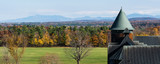 looking out at landscape of autumn woods with the Green Mountains of Vermont in the distance and the corner of the historic Farm Barn at Shelburne Farms a National Historic Site 