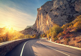 Fototapety Asphalt road in autumn forest at sunrise. Crimean mountains