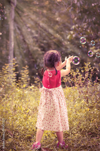 Asian girl catches soap bubbles on nature background. Outdoors. © kdshutterman
