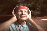 Elderly man with bandana, sunglasses and headset, listening rock and roll.