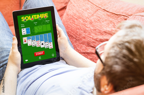 Plakat hipster on the sofa with solitaire app tablet