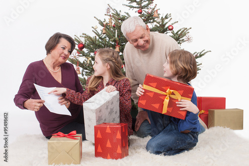 gro eltern mit enkel sitzen mit weihnachtsgeschenk. Black Bedroom Furniture Sets. Home Design Ideas