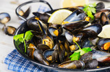 Copper pot of mussels garnished with lemon and herbs. - Fine Art prints