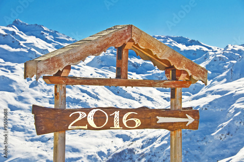 2016 written on a wooden direction sign, snow mountain landscape on the background