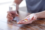 close up of male hands holding pills and water