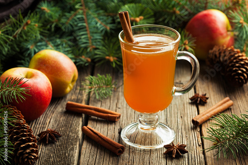 Naklejka Hot apple cider traditional winter season drink with cinnamon and anise. Homemade healthy organic warm spice beverage. Christmas or thanksgiving holiday decoration on vintage wooden background