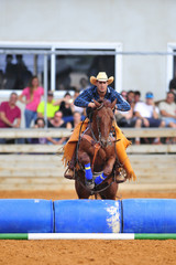 The rider jumping with horse over barrels