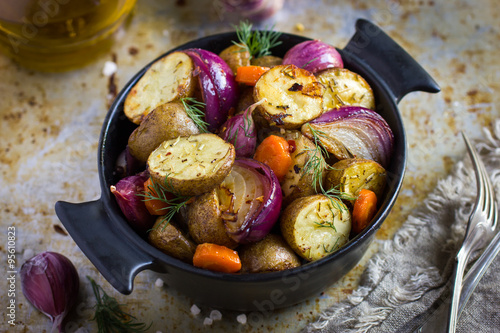 Poster roasted potatoes with  onions, carrot and garlic
