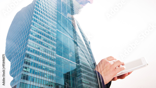 Papiers peints Londres Buisnessman typing on tablet double exposure with office building, white background