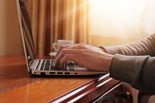 Close up of man's  hands working on laptop in luxury classic style interior